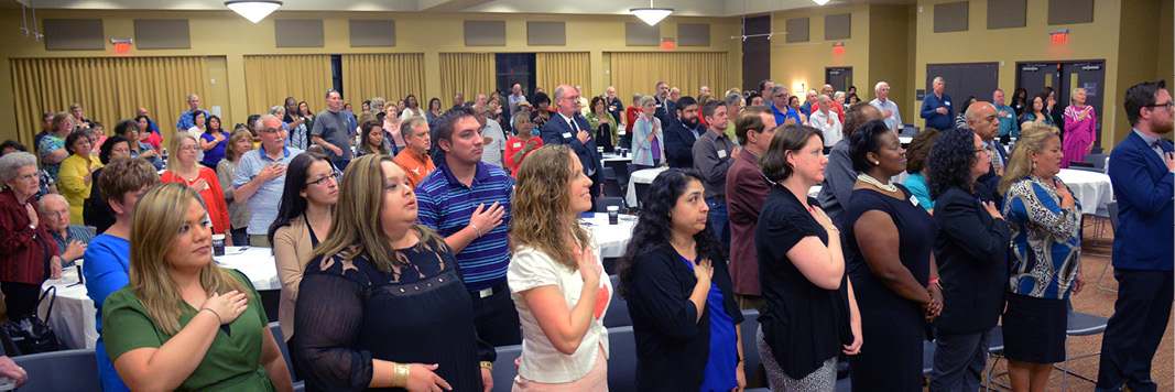 Greater Texas & Aggieland Credit Union's Annual Meeting is held every year. Pictured are members and employees in a large space pledging to the flag.
