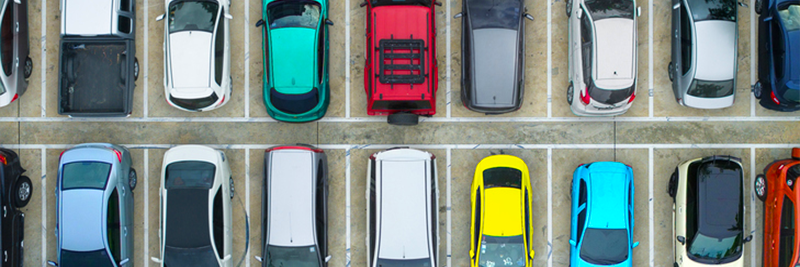 Picture: multiple vehicles of different colors lined up in a parking lot. Used to describe car shopping and leasing versus buying.