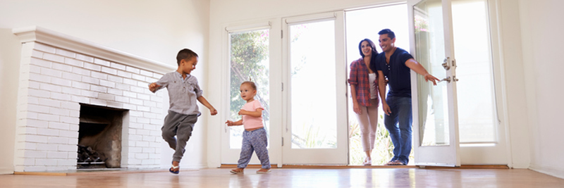 Parents open the door to their new home as children run around the empty living room.