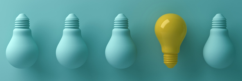 Picture: Five light bulbs in total. Four light bulbs are all green and positioned upside down while the fifth is yellow and positioned right-side up. Used to describe the differences between banks and credit unions.