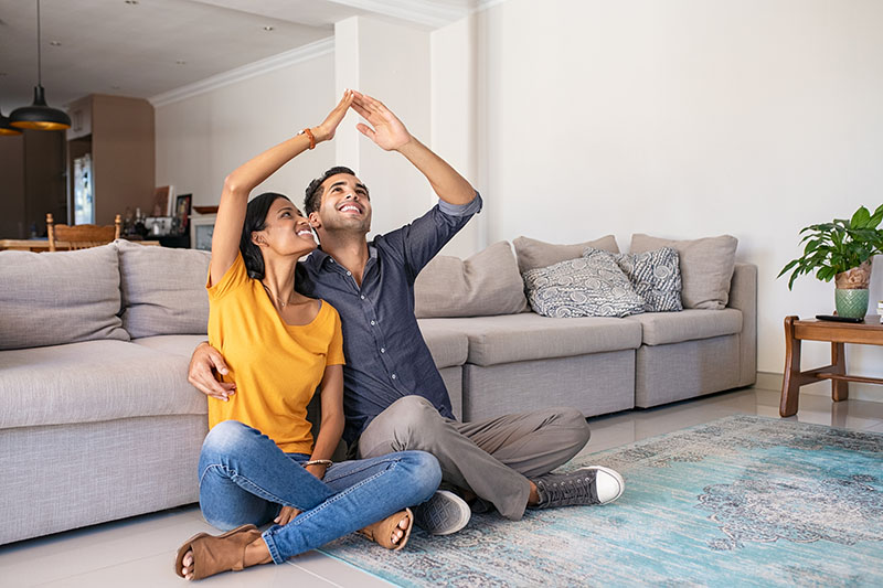 Couple sits in living room of new home.